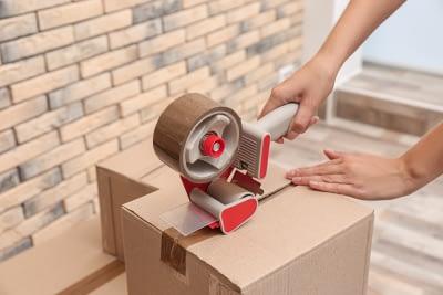 woman packing carton box indoors
